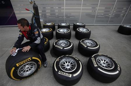 A Red Bull Formula One team member inspects Pirelli tyres near the pits at the Chinese F1 Grand Prix at the Shanghai International Circuit April 11, 2013. REUTERS/Carlos Barria