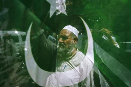 A supporter of the Pakistani religious political party Jamaat-e-Islami seen through a party flag during an anti-U.S. rally in Peshawar June 15, 2012. REUTERS/Khuram Parvez