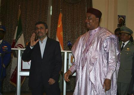 Iran's President Mahmoud Ahmadinejad (L) waves next to Niger's President Mahamadou Issoufou during a news conference in Niamey April 16, 2013. REUTERS/Stringer