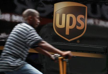 A bicycle delivery man rides past a UPS truck in New York's Times Square, July 23, 2012. REUTERS/Brendan McDermid