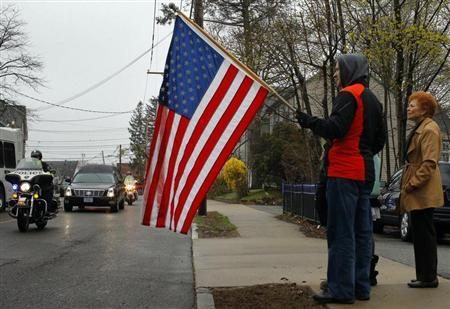 Richard Corapi holds a U.S. flag from a sidewalk while the hearse carrying the body of Massachusetts Institute of Technology (MIT) police officer Sean Collier passes by, in Stoneham, Massachusetts April 23, 2013. REUTERS/Brian Snyder