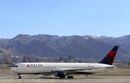 A Delta Airlines Boeing 767 passenger jet taxis past the Salt Lake City skyline, a day before the annual Thanksgiving Day holiday, at the Salt Lake City international airport, November 21, 2012. Picture taken November 21, 2012. REUTERS/George Frey