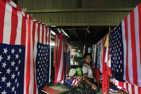 A girl hangs the newly made U.S flags at a shop in Yangon November 16, 2012. REUTERS/Minzayar