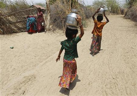 Village girls carry metal pitchers filled with water supplied by the government in Gujarat April 23, 2013. REUTERS/Amit Dave