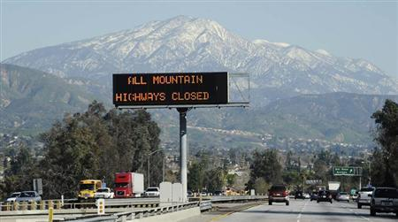 A sign near the San Bernardino Mountains warns of road closures during a manhunt for former LAPD officer Christopher Dorner, wanted in connection to the murders of three people, near the town of Angelus Oaks, California February 12, 2013. REUTERS/Gene Blevins