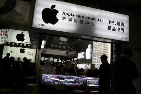 Customers and sales persons are seen at an Apple maintenance service store at a mobile phone market in Shanghai, January 24, 2013. REUTERS/Aly Song/Files