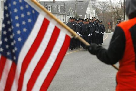 Richard Corapi holds a U.S. flag from a sidewalk as Massachusetts Institute of Technology police officers march away from the funeral of fellow MIT police officer Sean Collier in Stoneham, Massachusetts April 23, 2013. REUTERS/Brian Snyde