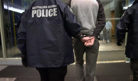Australian Federal policemen arrest the self-proclaimed leader of the international hacking group LulzSec, the collective that claimed responsibility for infiltrating and shutting down the CIA website, in this photo released by the Australian Federal Police on April 24, 2013. REUTERS/Australian Federal Police/Handout
