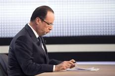 France's President Francois Hollande studies his notes before appearing on France 2 television prime time news broadcast for an interview at their studios in Paris, March 28, 2013. REUTERS/Fred Dufour/Pool