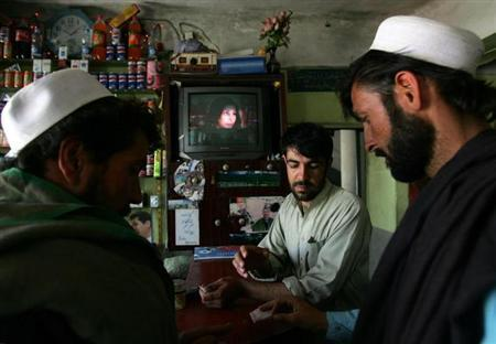 Afghan man (R) pays money for his meal at a restaurant as the Indian family series called 'Saas Bhi Kabhi Bahu Thi' runs on TV in Kabul, Afghanistan May 25, 2006. REUTERS/Ahmad Masood/Files