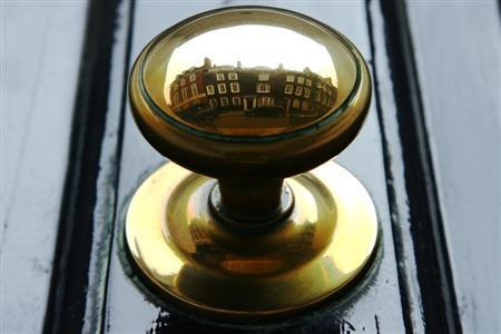 Houses are reflected in the door handle of a property in central London in this August 18, 2008 file photo. REUTERS/Luke MacGregor/Files