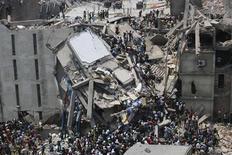 Люди ищут выживших после обрушения здания Rana Plaza в городе Савар, расположенном в 30 километрах от Дакки, 24 апреля 2013 года. Более 70 человек погибли, сотни получили ранения в результате обрушения восьмиэтажного здания в пригороде столицы Бангладеш в среду, сообщили власти. REUTERS/Andrew Biraj