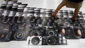 Женщина проходит по рекламе фотоаппаратов Canon в магазине в Токио, 23 апреля 2013 года. Японская Canon Inc снизила прогноз продаж компактных фотоаппаратов на текущий год, но увеличила ожидания по операционной прибыли, рассчитывая на более благоприятные колебания курса национальной валюты. REUTERS/Toru Hanai