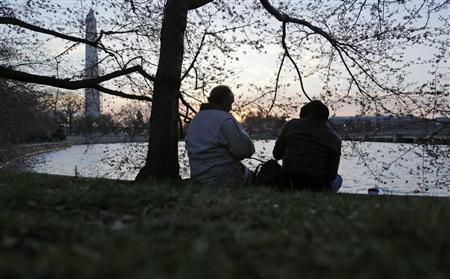 People drink coffee under cherry blossoms as the sun rises along the Tidal Basin in Washington, April 7, 2013. REUTERS/Jonathan Ernst