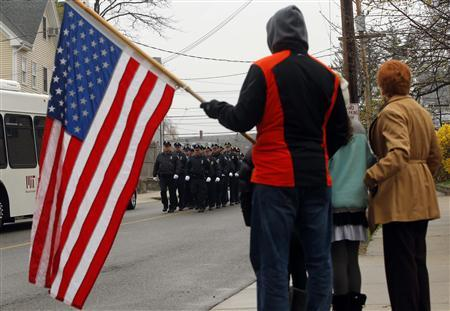 Richard Corapi holds a U.S. flag from a sidewalk as Massachusetts Institute of Technology police officers march away from the funeral of fellow MIT police officer Sean Collier in Stoneham, Massachusetts April 23, 2013. REUTERS/Brian Snyder