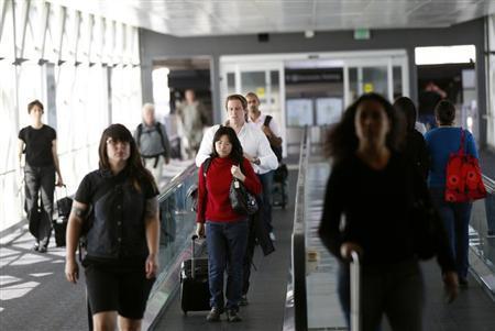 Airline passengers head to a flight at San Francisco International Airport in San Francisco, California April 22, 2013. REUTERS/Robert Galbraith