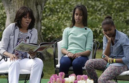 U.S. first lady Michelle Obama (L-R) reads the children's book ''Cloudy with a Chance of Meatballs'' as her daughters Malia and Sasha look on, during the annual Easter Egg Roll on the South Lawn of the White House in Washington, April 1, 2013. REUTERS/Jonathan Ernst