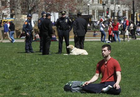 A man meditates in Copley Square Park as police officers congregate behind him after Boylston Street reopened to the public for the first time since the Boston Marathon bombings in Boston, Massachusetts April 24, 2013. REUTERS/Jessica Rinaldi