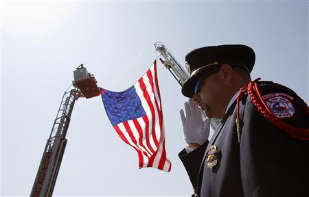 Killeen, Texas, fire-fighter Charles Layton salutes a procession of vehicles in honor of fallen fire-fighter Captain Kenneth ''Luckey'' Harris Jr. following funeral services at St. Mary's Catholic Church of the Assumption in West, Texas, April 24, 2013. REUTERS/Tim Sharp