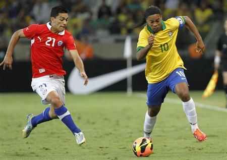 Brazil's Ronaldinho (R) races to the ball against Chile's Lorenzo Reyes during their international friendly soccer match in Belo Horizonte, April 24, 2013. REUTERS/Washington Alves