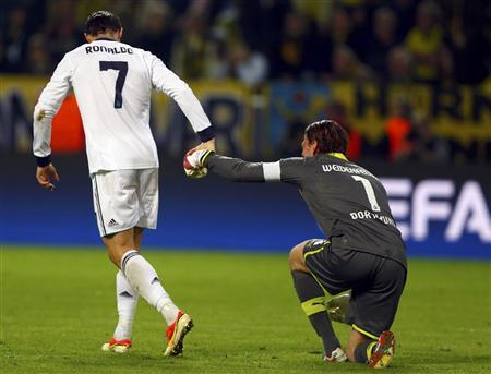 Real Madrid's Cristiano Ronaldo (L) helps Borussia Dortmund's goalkeeper Roman Weidenfeller to get up during their Champions League semi-final first leg soccer match in Dortmund April 24, 2013. REUTERS/Wolfgang Rattay