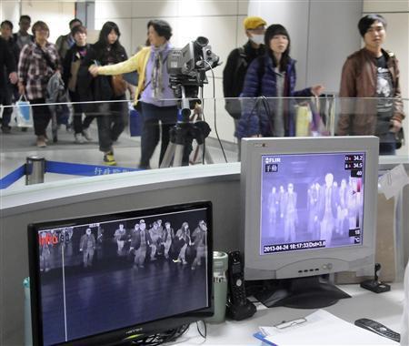 Passengers walk past temperature detectors at the entrance of Taoyuan International Airport, northern Taiwan, April 24, 2013. REUTERS/Stringer