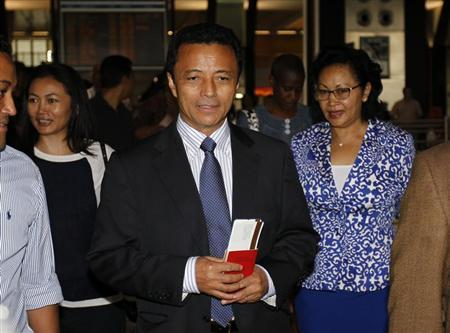 Former Madagascar leader Marc Ravalomanana and his wife Lalao (R) hold plane tickets after checking in at the O.R Tambo airport in Johannesburg, January 21, 2012. REUTERS/Siphiwe Sibeko