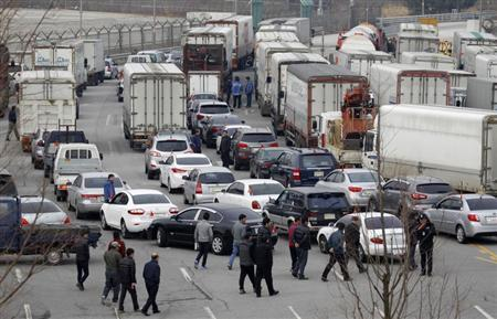 South Korean truck drivers walk to get in their trucks as they leave the South's CIQ (Customs, Immigration and Quarantine) office before going to the inter-Korean Kaesong Industrial Complex in North Korea, just south of the demilitarised zone separating the two Koreas, in Paju, north of Seoul, April 1, 2013. REUTERS/Lee Jae-Won
