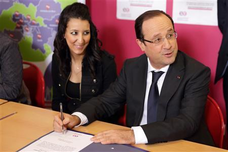 French President Francois Hollande (R) and an unidentified woman attend a ceremony for ''jobs of the future'' contracts with unemployed youths during a visit at the Gresilles neighbourhood in Dijon, March 11, 2013. REUTERS/Philippe Wojazer/Files