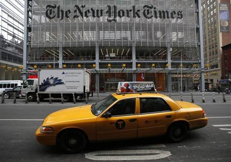 A taxi passes by in front of The New York Times head office in New York, February 7, 2013. REUTERS/Carlo Allegri
