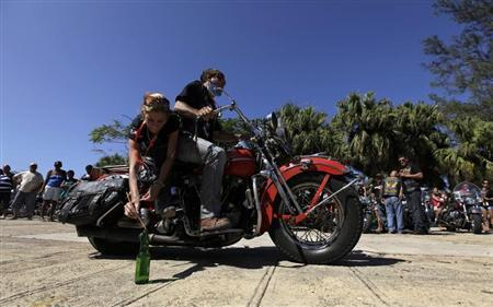 A man and a woman take part in a competition of riding skills in their Harley Davidson motorcycle during Cuba's Second Harley Davidson Convention February 9, 2013. REUTERS/Enrique De La Osa