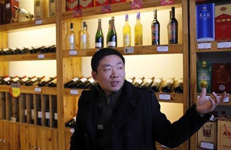 A man introduces his products inside a wine store at the business area of Ruzhou county, China's central Henan province, December 17, 2012. REUTERS/Aly Song