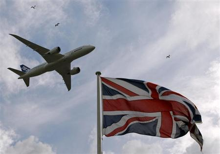 A Boeing 787 Dreamliner aircraft flies over a Union flag as it makes a salute to its engine makers Rolls-Royce in Derby, central England July 20, 2010. REUTERS/Darren Staples
