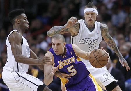 Miami Heat's Norris Cole (L) defends against Los Angeles Lakers' Steve Blake (C) as Heat teammate Chris Andersen (R) looks on in the first half of their NBA basketball game in Miami, Florida February 10, 2013. REUTERS/Andrew Innerarity