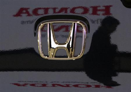 A visitor and the logo of Honda Motor Co are reflected on a Honda car at the company's headquarters in Tokyo January 30, 2009. REUTERS/Toru Hanai