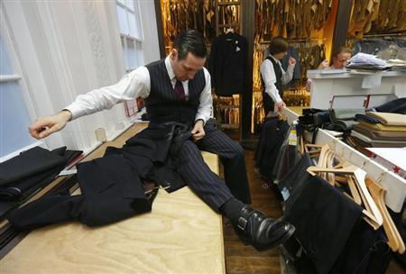 Leon Powell works on a garment at bespoke Savile Row tailors Anderson & Sheppard in central London February 14, 2013. REUTERS/Andrew Winning