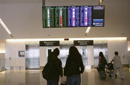Airline passengers look at a flight status board at San Francisco International Airport in San Francisco, California April 22, 2013. REUTERS/Robert Galbraith