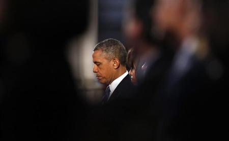 U.S. President Barack Obama and first lady Michelle Obama pray during an interfaith memorial service at the Cathedral of the Holy Cross for the victims of the Boston Marathon bombing in Boston, Massachusetts April 18, 2013. REUTERS/Kevin Lamarque