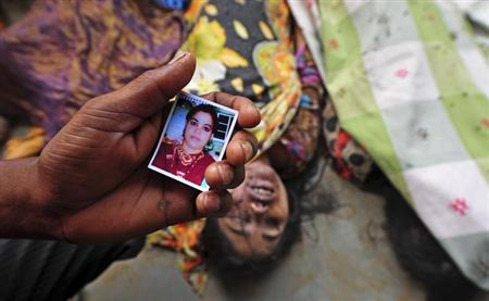 A relative holds a picture of a missing woman in front of the body of a garment worker who died in the collapse of the Rana Plaza building, in Savar, 30 km (19 miles) outside Dhaka April 25, 2013. REUTERS/Stringer