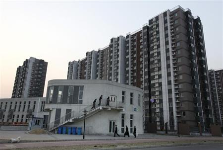 Security guards walk into a building in front of apartment blocks in Beijing March 22, 2013. REUTERS/Jason Lee