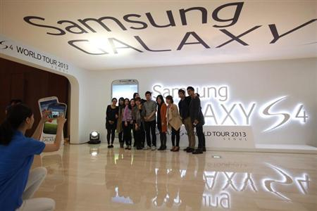 Visitors take a group photo next to a logo of Samsung Electronics Co Ltd's latest flagship smartphone S4 during its launch event at the company's headquarters in Seoul April 25, 2013. REUTERS/Kim Hong-Ji