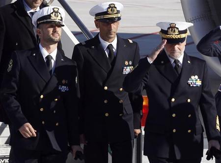 Italian marines Salvatore Girone (L) and Massimiliano Latorre (C) arrive with Italian Navy Chief of Staff Admiral Luigi Pinelli Mantelli at Ciampino airport in Rome, December 22, 2012. REUTERS/Alessandro Bianchi