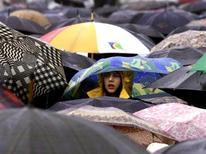 Девочка выглядывает из-под зонта во время акции протеста в Москве, 7 апреля 2001 года. Москву ждут пасмурные и дождливые выходные, прогнозируют синоптики. CVI