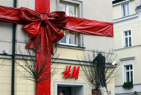 A worker prepares light decorations at a high street H&M clothing store wrapped up in a giant ribbon, ahead of its grand opening one month before Christmas in Warsaw November 24, 2010. REUTERS/Kacper Pempel/Files