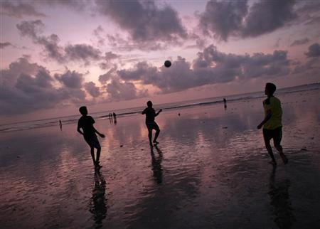 People play football at Juhu Beach against the backdrop of monsoon clouds in Mumbai August 23, 2012. REUTERS/Danish Siddiqui