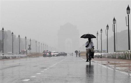 A man holds an umbrella whilst cycling as it rains in New Delhi August 24, 2012. REUTERS/Adnan Abidi/Files