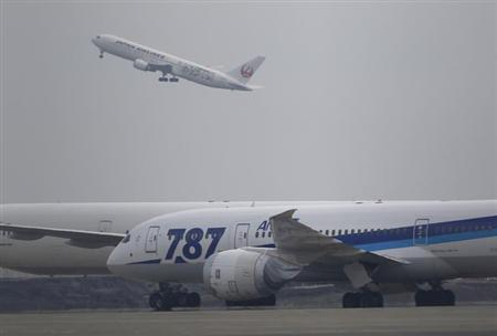 A Japan Airlines aircraft (top L) takes off as an All Nippon Airways' Boeing Co's 787 Dreamliner plane parks on the tarmac at Haneda Airport in Tokyo February 4, 2013. REUTERS/Toru Hanai