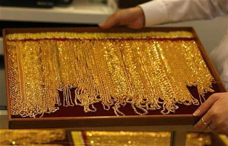 A shop attendant carries a tray of gold necklaces at a jewellery store in Singapore September 18, 2008. REUTERS/Vivek Prakash/Files