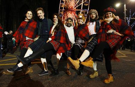 Revellers pose for photographers during the Hogmanay (New Year) street party celebrations in Edinburgh, Scotland December 31, 2012. REUTERS/David Moir
