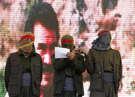 Masked supporters of jailed Kurdish rebel leader Abdullah Ocalan stand on the stage as one reads a statement during a gathering to celebrate Newroz in the southeastern Turkish city of Diyarbakir March 21, 2013. REUTERS/Umit Bektas